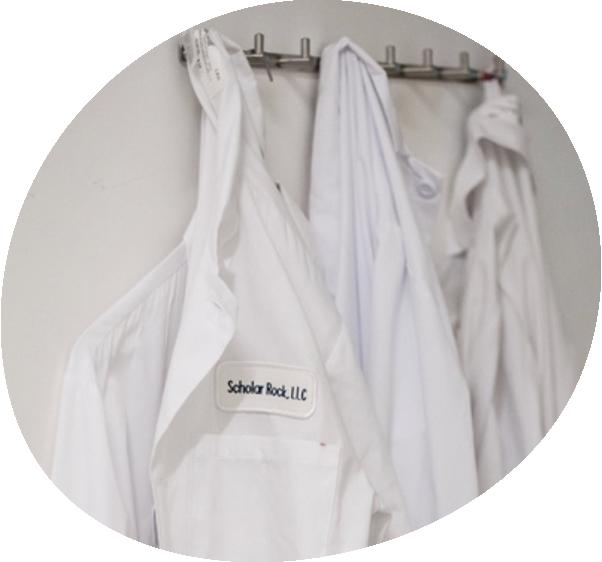 Three lab coats hanging on hooks